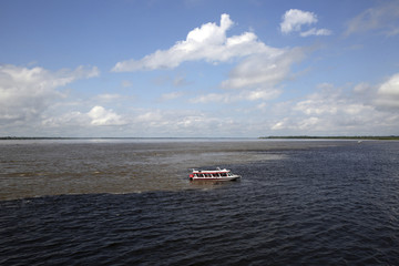 """A tourist boat rides past the """"the meeting of the rivers"""" in Manaus"""