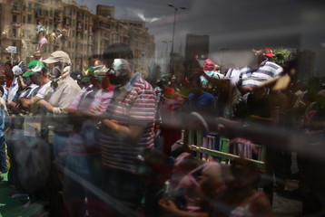 Protesters are seen reflected in a window glass as they attend Friday prayers at Tahrir Square in Cairo