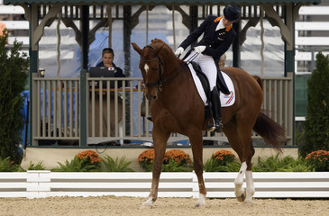 Cornelissen of the Netherlands, riding Jerich Parzival, looks at the mouth of her horse after elimination bell was rung during Grand Prix Dressage Championship in Lexington
