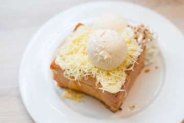 Chesse toast with ice-cream on white dish.