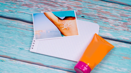 Photo of a girl on the beach and a sun block from sunburn on a wooden table