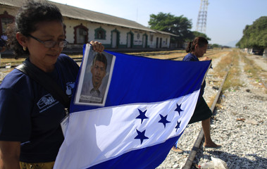 Activists from a 13-member caravan hold a Honduras flag near pictures of missing migrants, in Ixtepec