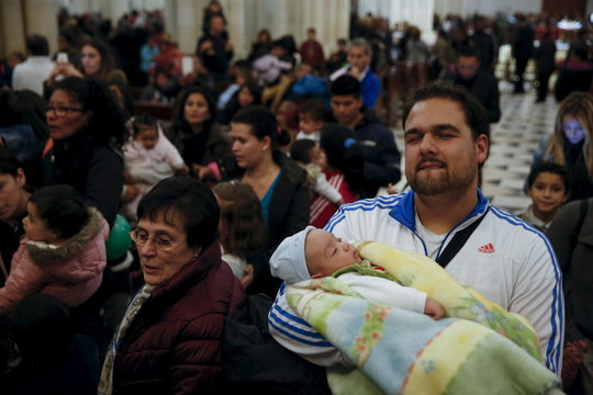 People wait in line to have a picture of their children taken on the lap of one of the Three Wise Men during a distribution of free toys for low-income families at Almudena Cathedral in Madrid