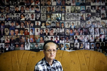 Hajra Catic poses under pictures of victims of the genocide in Tuzla