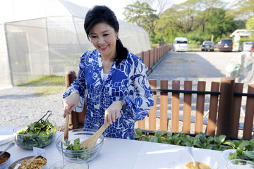 Ousted former Thai PM Yingluck Shinawatra prepares a salad with vegetables from her garden while receiving foreign media at her house in Bangkok