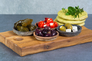 Mediterranean appetizer antipasti tapas bowls with green and calamata olives, feta cheese, stuffed pepper with garlic pita bread, herbs on wooden plank