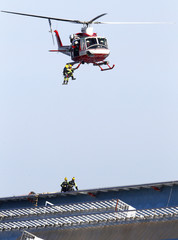 Firefighters hangs from a chopper over the Costa Concordia cruise ship which ran aground off the west coast of Italy at Giglio island