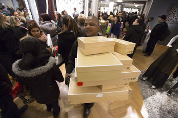 Sales assistant carries boxes of shoes in Macy's during Black Friday sales in New York
