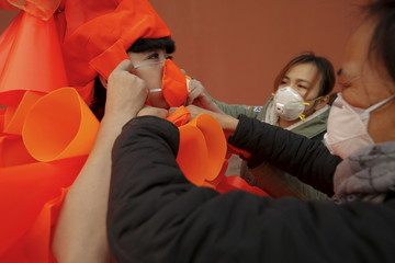 Assistants help Chinese artist Kong Ning with her costume made of hundreds of orange plastic blowing horns during her art performance raising awareness of the hazardous smog in a historical part of Beijing