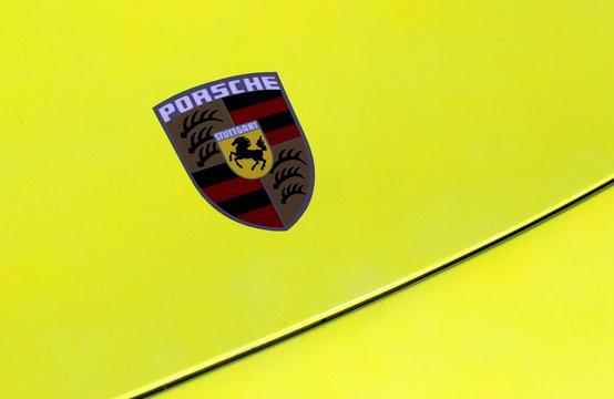 The Porsche logo is seen on the hood of a sports car during the Porsche Rennsport Reunion V at Laguna Seca Raceway near Salinas