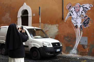 A nun takes a picture of a large drawing  of Pope Francis depicting him as a superhero on a wall near the Vatican