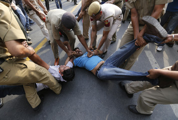 Police try to detain supporters of Aam Aadmi Party during a protest outside the residence of India's PM Singh in New Delhi