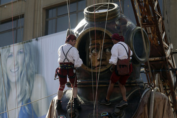Crew members check the helmet of a giant puppet of a diver in downtown Santiago during a performance by French street theatre company Royal de Luxe