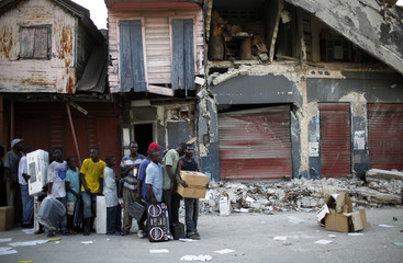 Looters under arrest wait in line for the arrival of a police vehicle in a commercial area of downtown Port-au-Prince