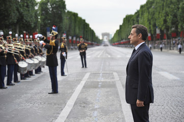 France's President Sarkozy listens to a military brass band during the annual Bastille Day military parade in Paris