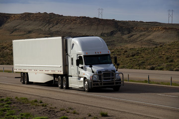 A white Freightliner Cascadia Semi-Tractor pulls a white trailer along Interstate 80 in Rural Wyoming on May 4th, 2017.