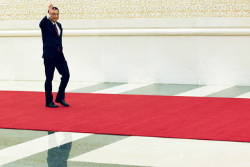 China's Premier Li Keqiang waves as he arrives at a news conference following the closing ceremony of National People's Congress at the Great Hall of the People in Beijing