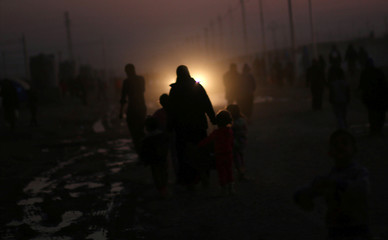 Displaced Iraqis, who fled the Islamic State stronghold of Mosul, walk at Khazer camp