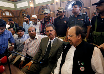 Waseem Akhtar, mayor nominee of Muttahida Qaumi Movement (MQM) political party, waits with others before casting his ballot for mayor at the halls of the Municipal Corporation Building in Karachi
