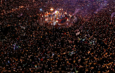 """Hindu devotees hold earthen lamps and torches to perform prayers called """"Aarti"""" during the celebrations to mark the Navratri festival, in which devotees worship Hindu goddess Durga, at Surat"""