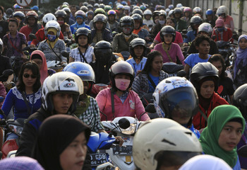 Women workers ride motorcycles in front of their shoes factory as they return home, in Tangerang