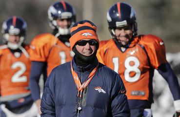 Denver Broncos head coach John Fox walks in front of Peyton Manning as Denver Broncos practice for Super Bowl in Florham Park