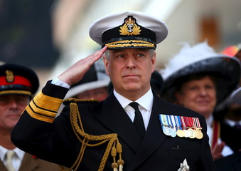 Britain's Prince Andrew salutes the marching Armed Forces as he attends the Armed Forces Day in Guildford
