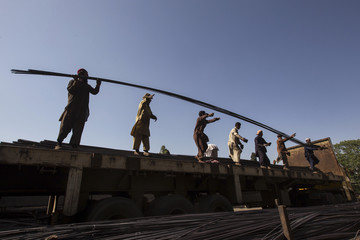 Workers unload iron rods at a factory in Islamabad