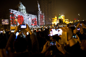 Visitors take pictures and videos during a fireworks explode over Oriental Pearl Tower as part of a New Year countdown celebration on the Bund in Shanghai