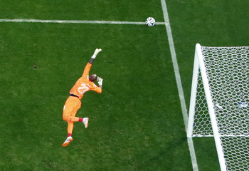 Algeria's goalkeeper Mbolhi dives for the ball during the 2014 World Cup round of 16 game between Germany and Algeria in Porto Alegre