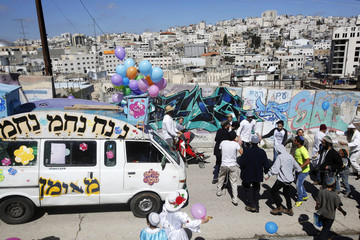 Israeli settlers dance as Hebron city is seen in the background during celebrations marking the Jewish holiday of Purim in the occupied West Bank city of Hebron