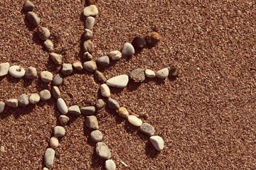 солнце на песке летом выложено из камней