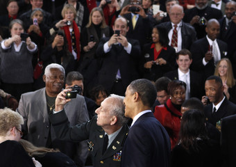 An audience member uses his camera to take a picture of himself with U.S. President Barack Obama at Forsyth Technical Community College in Winston-Salem, North Carolina