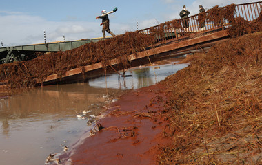 A fireman crosses a pontoon bridge next to broken bridge in the flooded village of Kolontar