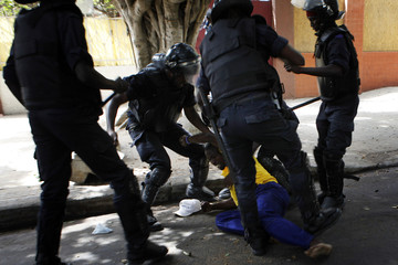 Riot police beat a demonstrator during a demonstration in Senegal's capital Dakar