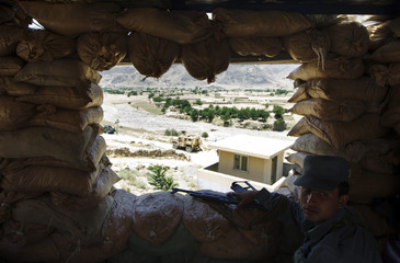 An Afghan National Police officer mans an observation post during an advising visit from U.S. Army soldiers of Bravo troop, 1st Squadron of the 75th Cavalry Regiment, 2nd Brigade, 101st Airborne Division at their base near the city of Mara Wara in Afghanis