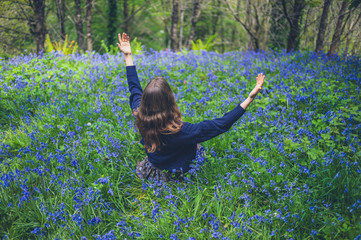 Young woman raising her arms in bluebell meadow