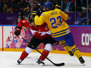 Canada's Crosby is grabbed by Sweden's Edler during second period of their men's ice hockey gold medal match at Sochi 2014 Winter Olympic Games