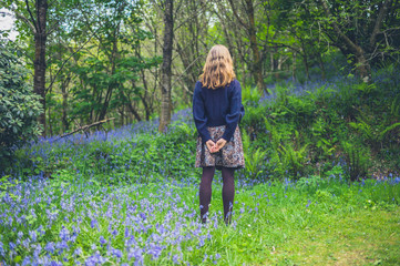 Woman with hands behind her back in meadow