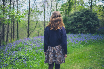 Woman walking in forest with bluebells