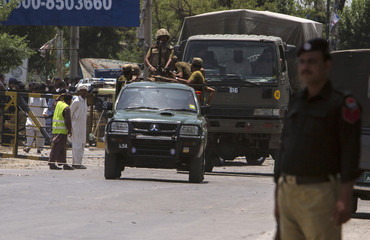 Soldiers leave after visiting the site of a bomb attack on a security forces vehicle in Fateh Jang