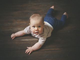 Little baby on wooden floor