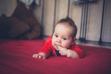 Little baby in red on a bed
