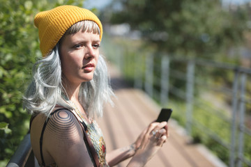 Young lady with a yellow hat using her phone