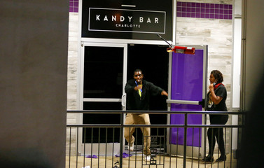 A looters throws a fire extinguisher from the doorway to the club Kandy Bar in uptown Charlotte, NC during a protest of the police shooting of Keith Scott, in Charlotte