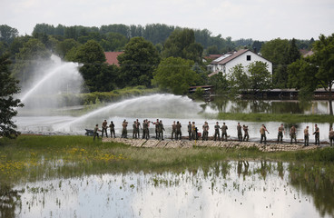 German army Bundeswehr soldiers carry sandbags to build a barrier against flooded Danube river in the eastern Bavarian village of Niederalteich