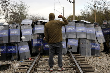 A stranded migrant demonstrates in front of a Macedonian police cordon as they clash after a migrant was electrocuted and badly burned when he climbed on top of a train wagon, near the village of Idomeni
