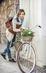 Young woman posing with retro bicycle with wicker garden baskets