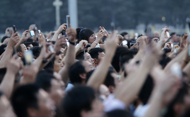 Visitors take pictures of a flag lowering ceremony at Tiananmen Square in Beijing