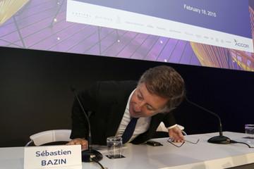 French hotel operator Accor CEO Sebastien Bazin checks his name card before the company's 2014 results presentation in Paris